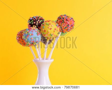 Sweet cake pops in vase on yellow background