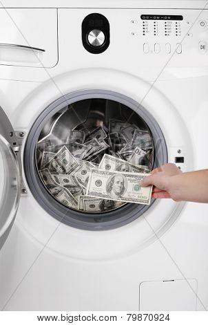Female putting money into washing machine, closeup