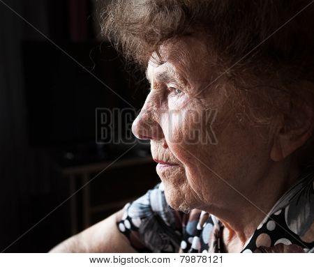 Old woman looking away. Elderly female at home
