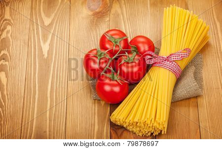 Pasta and tomatoes on wooden table background with copy space