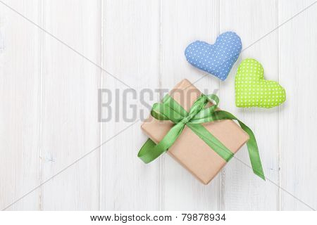 Valentines day toy hearts and gift box over wooden table background