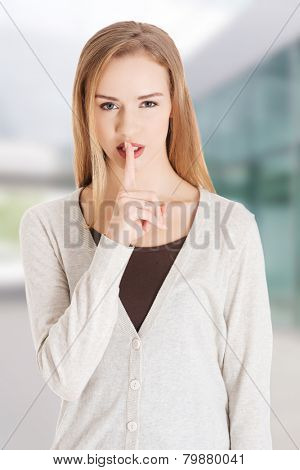 Beautiful woman with finger on lips