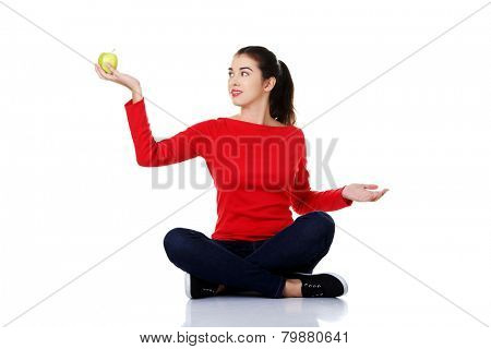 Woman sitting cross-legged holding an apple.