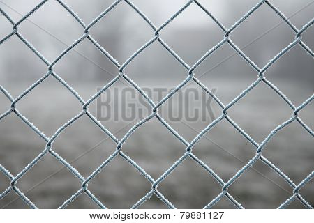 Frozen wire fence in winter frost
