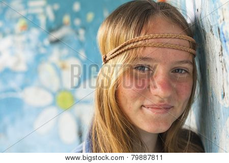 Portrait of young cute girl hippie, old dirty wall on the background.