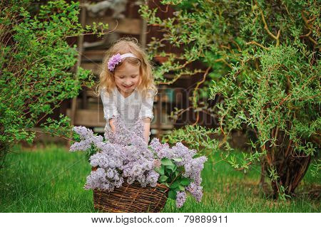 horizontal portrait of cute child girl playing in spring garden with basket of lilacs