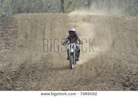 Motocross Racer Riding Down A Dirt Hill