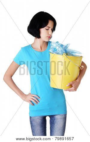 Pensive woman holding bucket of plastic rubbish.