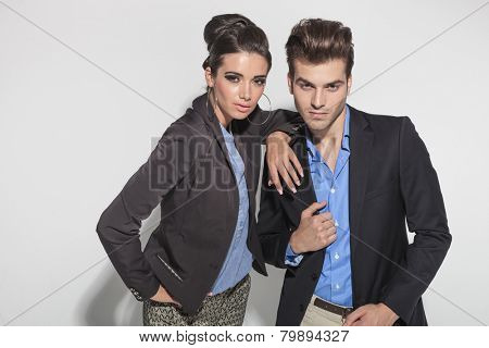 Fashion couple posing close to each other. The woman is holding her arm on his shoulder while he is fixing his jacket.
