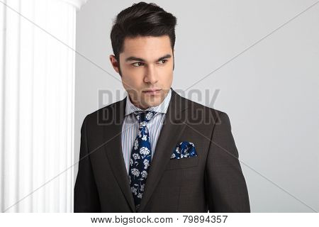 Close up picture of a young elegant business man looking away from the camera, near a white column.