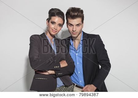 Beautiful young woman standing next to her lover with her hands crossed, both looking at the camera.