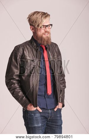 Portrait of a happy young beard man smiling while holding both hands in his pocket, looking away from the camera.