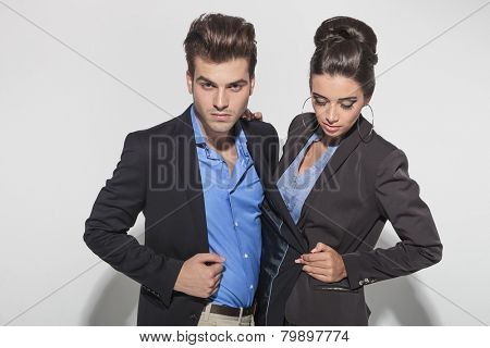 Young fashion woman pulling her lovers jacket while looking down.