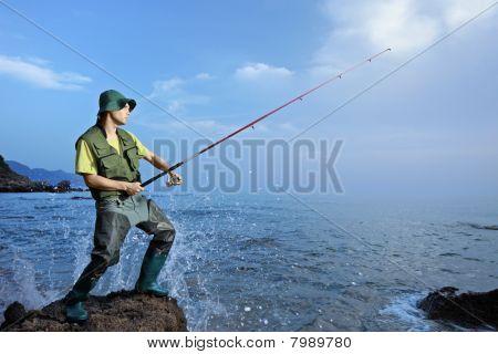 A fisherman fishing at the sea