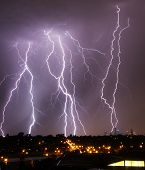 foto of storms  - Storm with lightning strikes over Melbourne city skyline - JPG