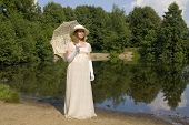 picture of century plant  - Young woman in white historical dress of XIX century with white umbrella in white hat near lake - JPG