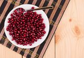 picture of wallow  - red grains of a pomegranate on the wooden background - JPG