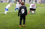picture of football pitch  - Young kids during a boys soccer match on green soccer pitch - JPG