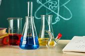 picture of chemistry  - Desk in chemistry class with test tubes on green blackboard background - JPG