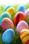 stock photo of sunny season  - Close Up Of Many Colorful Easter Eggs On Sunny Green Gras For Easter Or Seasons Greetings