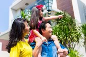 stock photo of in front  - Asian Chinese family of parents and child standing proud in front of  modern home - JPG