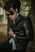 foto of down jacket  - Portrait of a young casual man looking down while leaning on a tree - JPG