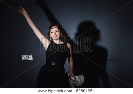 beautiful girl in the studio dressed , retro outfit throws money
