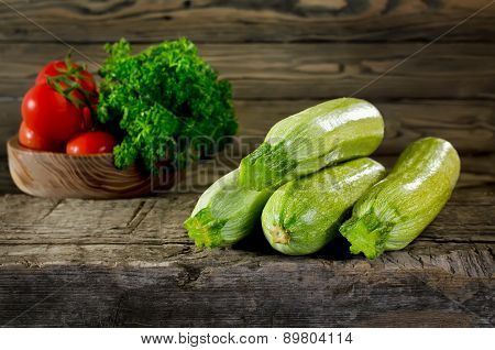Zucchini, Tomatoes And Parsley On Wooden Background. Zucchini Closeup