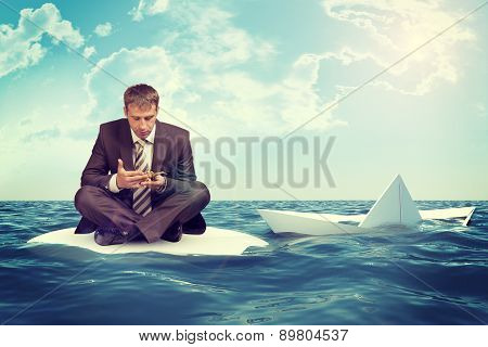 Businessman with sinking paper boat