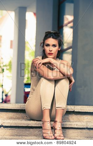 young woman in golden pants and sandals sit on stairs , outdoor shot, retro colors