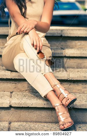 young woman in golden pants and sandals sit on stairs with sunglasses in hand, outdoor shot