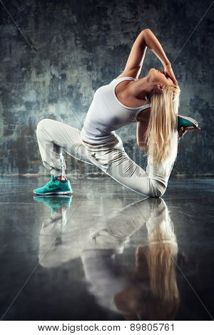 Young woman modern dancer stretching legs. On dark stone wall background.