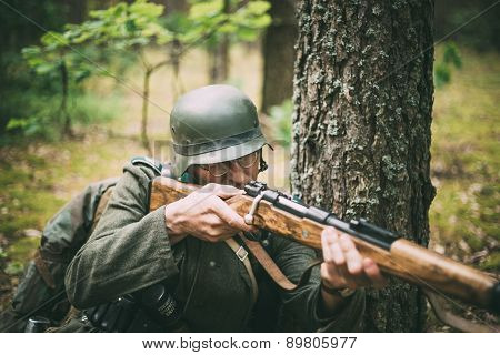 Unidentified re-enactor dressed as German soldier aiming a rifle