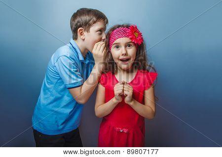 Teen boy whispering in the ear of teen girl on a gray  backgroun