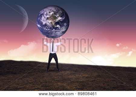 Businessman carrying the world against sunset over field