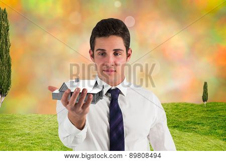 Businessman standing with hand out against glowing lights behind field