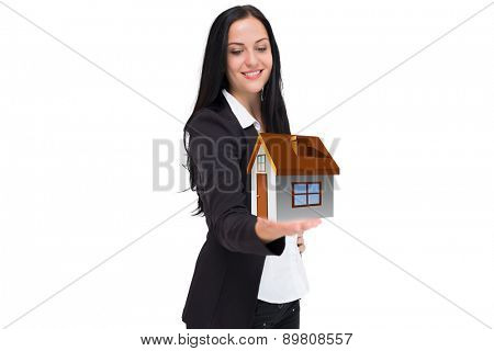 Pretty businesswoman presenting with hand against house