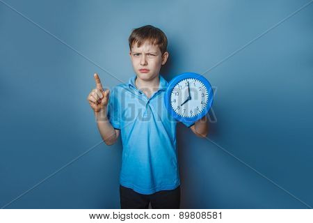 Boy teenager European appearance ten years holding a wall clock
