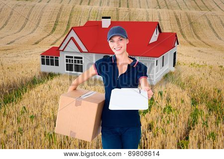 Happy delivery woman holding cardboard box and clipboard against rural fields