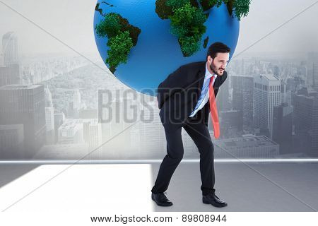 Businessman carrying the world against city scene in a room