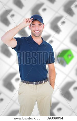 Portrait of happy delivery man wearing cap against one green roofed 3d house surrounded by many