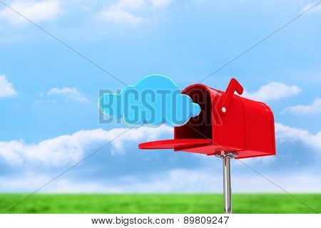 Red email postbox against field and sky