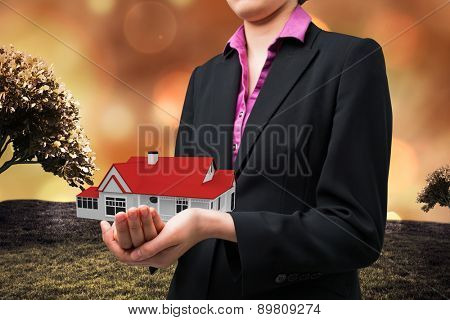 Businesswomans holding hands out against field against glowing lights