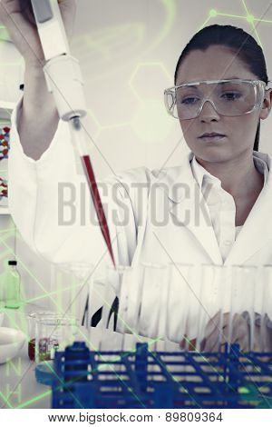 Gorgeous female biologist holding a manual pipette with sample from test tubes against science and medical graphic