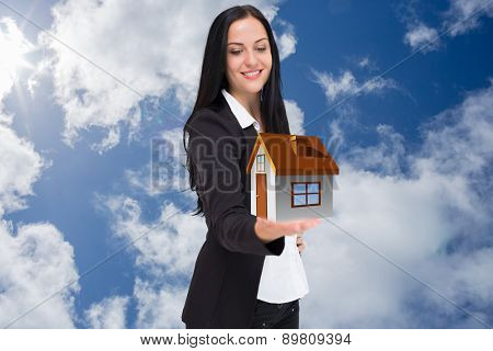 Pretty businesswoman presenting with hand against bright blue sky with clouds