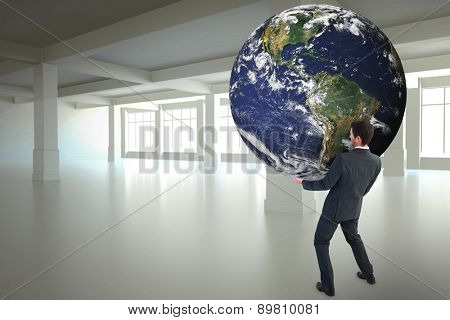 Businessman carrying the world against white room with windows