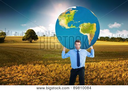 Businessman carrying the world against field with tree and city on the horizon