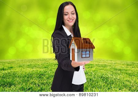 Pretty businesswoman presenting with hand against field against glowing lights
