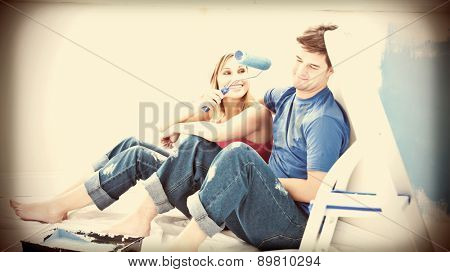 Charming couple relaxing after painting a room in their new house
