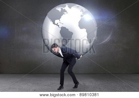 Businessman carrying the world against grey room